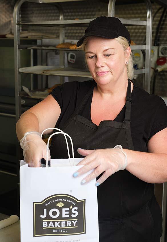 Woman placing sandwich in Joe's Bakery Bag